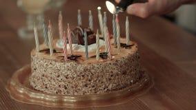 Mano maschio che accende le candele in torta di compleanno archivi video