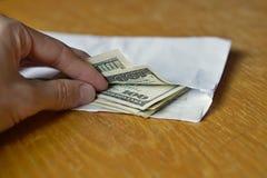 Mano maschio che apre una busta bianca in pieno dei dollari americani (USD, dollari americani) sulla tavola di legno come simbolo Fotografia Stock