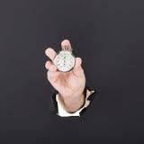 Mano maschio che attraversa i precedenti di carta e che tiene orologio antico Di alta risoluzione Immagini Stock Libere da Diritti