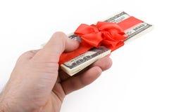Mano maschio che dà via pacchetto delle note del dollaro immagine stock