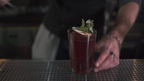 Mano maschio che decora cocktail fresco con la menta e l'arancia facendo uso delle tenaglie sulla fine del contatore della barra  video d archivio