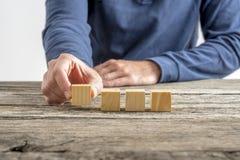 Mano maschio che dispone quattro cubi di legno in bianco in una fila Fotografie Stock
