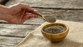 Mano maschio che giudica cucchiaio di legno pieno dei semi nutrizionali di Chia Immagine Stock