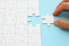 mano maschio che mette l'ultimo pezzo nel puzzle fotografie stock libere da diritti
