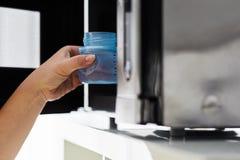 Mano maschio che mette un biberon in una microonda Fotografie Stock Libere da Diritti