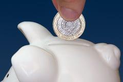 Mano maschio che mette una moneta nel porcellino salvadanaio Fotografia Stock Libera da Diritti