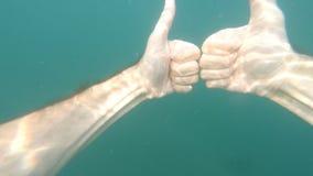 Mano maschio che mostra i pollici sul gesto del segno su fondo subacqueo blu con le bolle e la luce solare Gesti e segni stock footage
