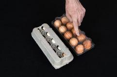 Mano maschio che mostra una scatola delle uova di plastica invece della scatola del cartone in pieno di uova di gallina sul fondo fotografia stock libera da diritti