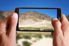 Mano maschio che prende foto del paesaggio della montagna della roccia con la cellula, telefono cellulare Fotografie Stock Libere da Diritti