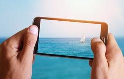 Mano maschio che prende foto della barca a vela, del mare, del sole, del blu, del mare, dell'orizzonte e dell'oceano con la cellu Fotografia Stock Libera da Diritti