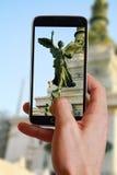 Mano maschio che prende foto della statua nella costruzione italiana di governo a Roma con la cellula, telefono cellulare Viaggio Immagini Stock