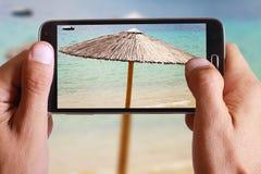 Mano maschio che prende foto di Straw Beach Umbrella e della barca con la cellula, telefono cellulare Immagine Stock