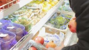 Mano maschio che seleziona granato fresco in supermercato Frutti d'acquisto dell'uomo al deposito archivi video