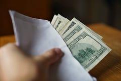 Mano maschio che tiene e che passa una busta bianca in pieno dei dollari americani (USD, dollari americani) come simbolo del tras Fotografia Stock