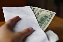Mano maschio che tiene e che passa una busta bianca in pieno dei dollari americani (USD, dollari americani) come simbolo del tras Fotografie Stock Libere da Diritti