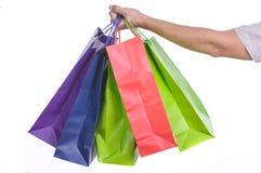 Mano maschio che tiene i sacchetti della spesa variopinti Fotografia Stock