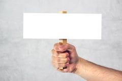 Mano maschio che tiene il segno in bianco dell'insegna del modello come spazio della copia Immagini Stock Libere da Diritti