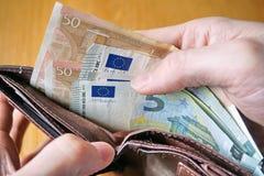 Mano maschio che tiene un portafoglio di cuoio e che ritira moneta europea (euro, EUR) Fotografia Stock Libera da Diritti