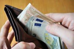 Mano maschio che tiene un portafoglio di cuoio e che ritira moneta europea (euro, EUR) Immagine Stock