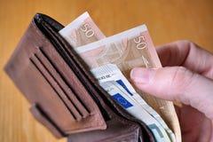 Mano maschio che tiene un portafoglio di cuoio e che ritira moneta europea (euro, EUR) Fotografia Stock