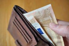 Mano maschio che tiene un portafoglio di cuoio e che ritira moneta europea (euro, EUR) Immagine Stock Libera da Diritti