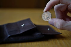 Mano maschio che tiene una moneta bronzea di dieci Yen Yen giapponesi, JPY e ritirante quella dal portafoglio di cuoio Fotografia Stock