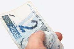 Mano maschio che tiene valuta nazionale del Brasile Fotografie Stock