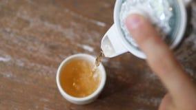 Mano maschio che versa tè verde sano dalla teiera in tazza d'annata sulla Tabella di legno Concetto di cerimonia del cinese tradi stock footage