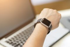 Mano maschio con l'orologio astuto sul polso, controllante tempo di lavorare, finire di lavorare immagine stock libera da diritti