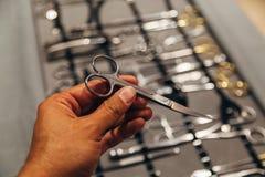 Mano maschio con le forbici chirurgiche su fondo del corredo degli strumenti chirurgici e degli strumenti fotografia stock libera da diritti
