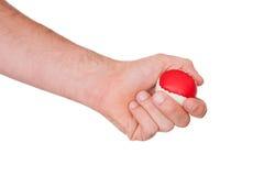 Mano maschio con una palla rossa e bianca Immagini Stock