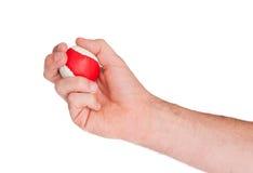 Mano maschio con una palla rossa e bianca Immagine Stock