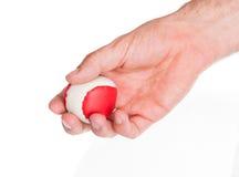 Mano maschio con una palla rossa e bianca Fotografia Stock