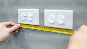 Mano maschio facendo uso della misura di nastro su sbocco elettrico fotografie stock libere da diritti