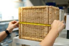 Mano maschio facendo uso della misura di nastro sulla scatola tessuta di legno immagine stock libera da diritti