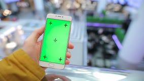 Mano maschio facendo uso dello smartphone con lo schermo verde nel centro commerciale archivi video