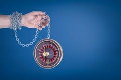 Mano maschio incatenata alle roulette su fondo blu fotografia stock libera da diritti