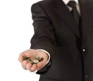Mano maschio nelle monete della holding del vestito Immagine Stock