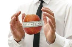 Mano masculina alrededor de la manzana envuelta con la cinta métrica Imagen de archivo
