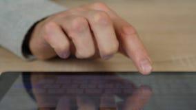 Mano masculina con cierre de la tableta para arriba Sirva el golpecito con el finger para buscar algo en Internet metrajes