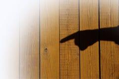 Mano masculina con el dedo índice en un fondo de madera Fotografía de archivo libre de regalías