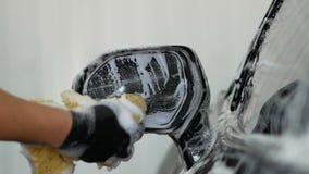 Mano masculina con el espejo retrovisor del coche del lavado de la esponja de la espuma almacen de metraje de vídeo