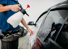 Mano masculina con el espray, instalación del tinte de la ventanilla del coche foto de archivo libre de regalías