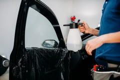 Mano masculina con el espray, instalación del tinte de la ventanilla del coche fotografía de archivo libre de regalías