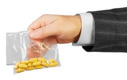 Mano masculina con el paquete de drogas Foto de archivo