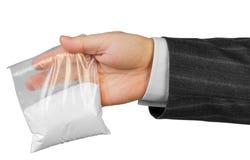 Mano masculina con el paquete de drogas Foto de archivo libre de regalías