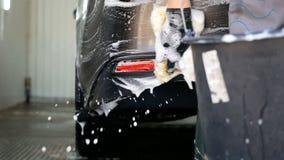 Mano masculina con el parachoques trasero del coche del lavado de la esponja de la espuma almacen de metraje de vídeo