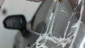 Mano masculina con el tejado del coche del lavado de la esponja de la espuma y las ventanas laterales almacen de video