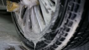 Mano masculina con la rueda de coche de la esponja de la espuma que se lava almacen de metraje de vídeo