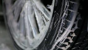 Mano masculina con la rueda de coche de la esponja de la espuma que se lava Cámara lenta almacen de video